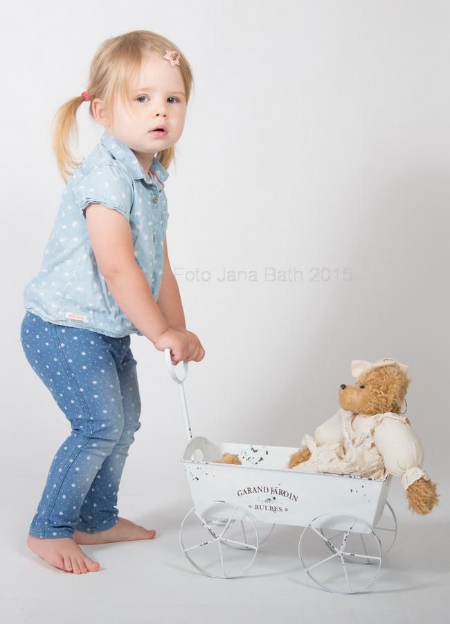 kleines Mädchen mit Ziehwaagen und Teddy