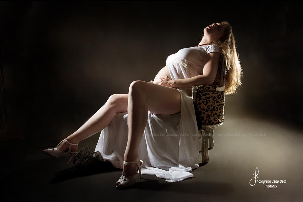 Babybauch auf kleiner Couch im weißen Kleid - Foto Jana Bath Rostock