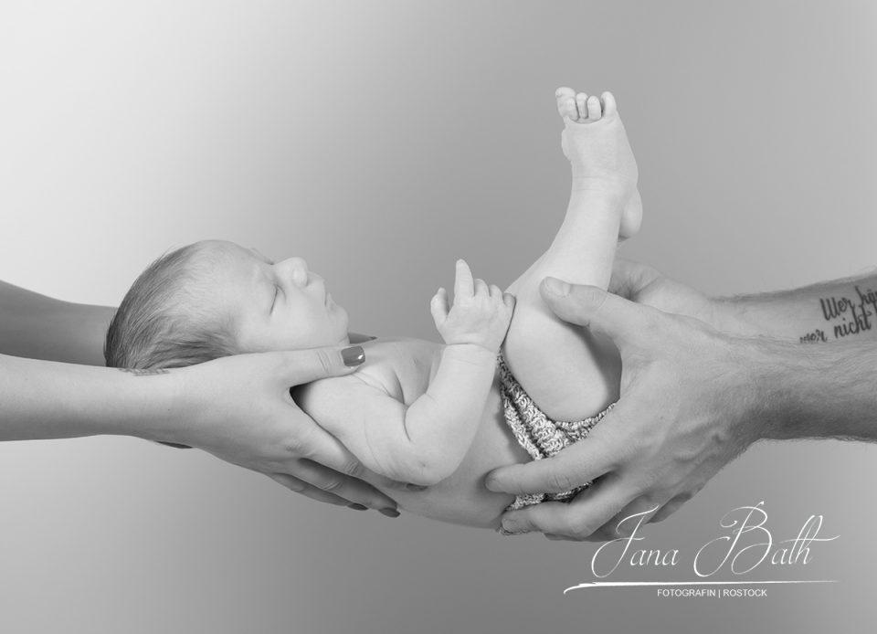 Baby 5 Wochen in Mama und Papas Händen